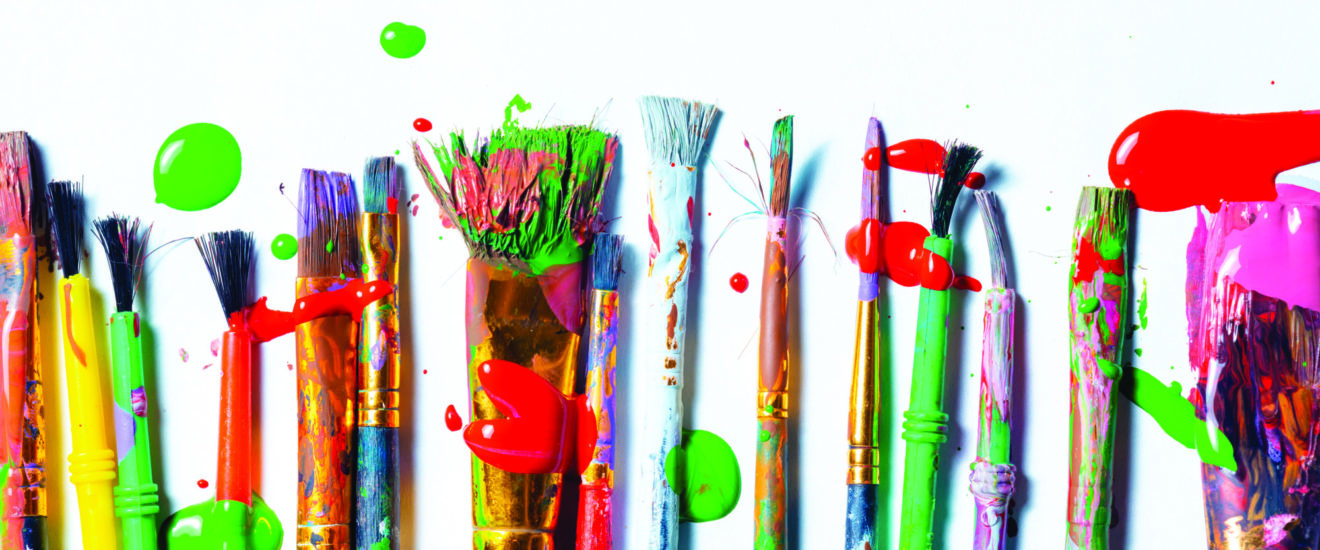 Row Of Messy Colorful Paint Brushes On Isolated White Background